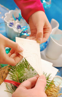 stock-photo-hands-of-family-members-sharing-with-traditional-christmas-eve-wafer-above-the-festive-table-90129352
